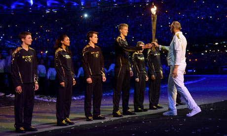 Sir Steve Redgrave hands the torch to the young athletes who are to light the cauldron during the London 2012 opening ceremony. Photograph: Owen Humphreys/PA